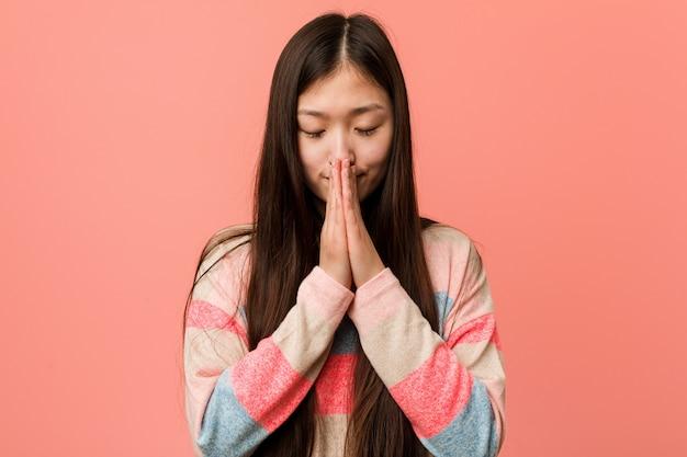 La mujer china fresca joven que lleva a cabo las manos adentro ruega cerca de boca, se siente confiado.