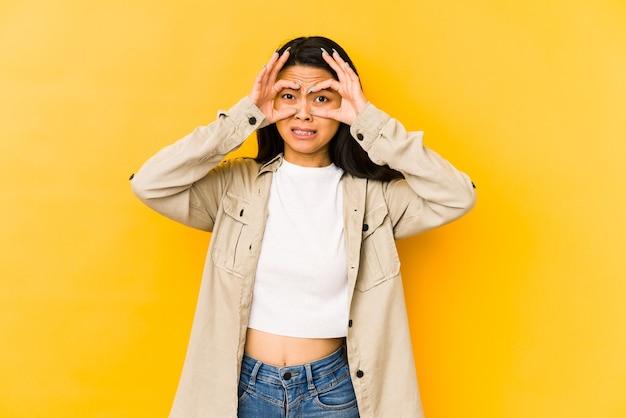 Mujer china joven aislada en un fondo amarillo manteniendo los ojos abiertos para encontrar una oportunidad de éxito.