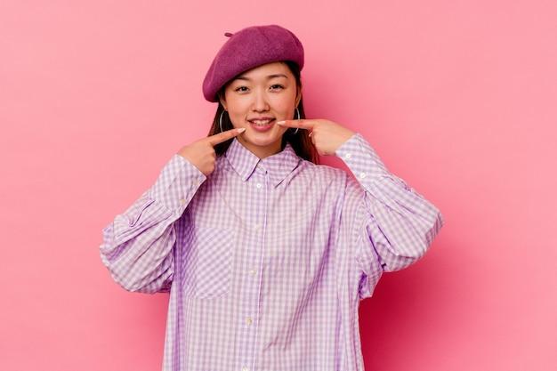 La mujer china joven aislada en el fondo rosado sonríe, señalando con el dedo a la boca.