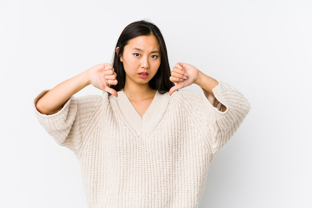 Mujer china joven aislada mostrando el pulgar hacia abajo y expresando aversión.