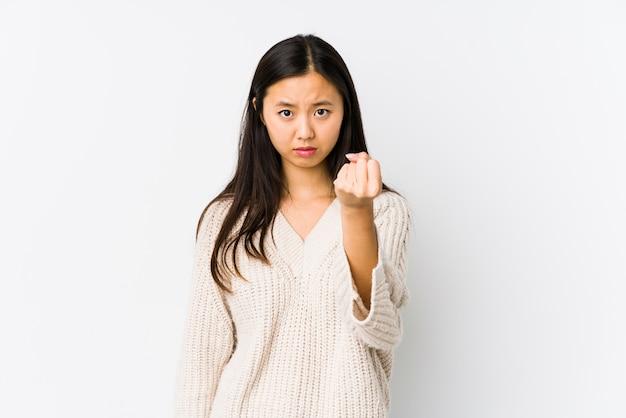 La mujer china joven aislada mostrando el puño con la expresión facial agresiva.