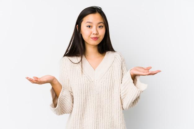 La mujer china joven aisló dudar y encogerse de hombros en gesto inquisitivo.