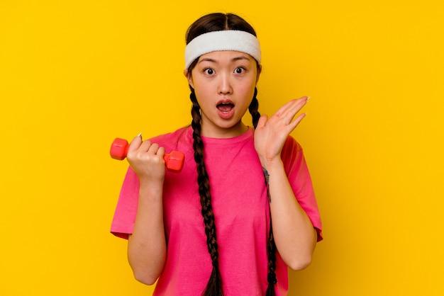 Mujer china joven deporte aislada sobre fondo amarillo sorprendida y conmocionada.