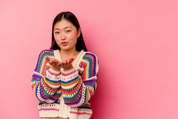 Mujer china joven doblando los labios y sosteniendo las palmas de las manos para enviar un beso al aire.