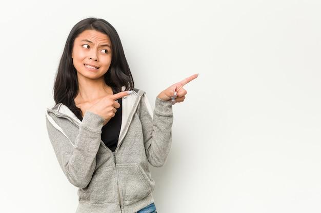 Mujer china joven fitness sorprendido señalando con los dedos índices a un espacio de copia.