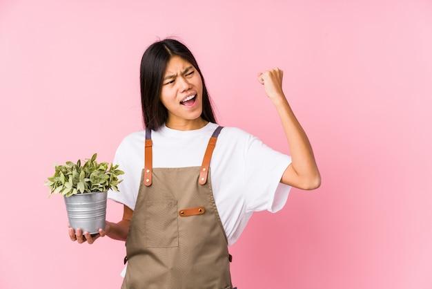 La mujer china joven del jardinero que sostenía una planta aisló levantar el puño después de una victoria, concepto del ganador.