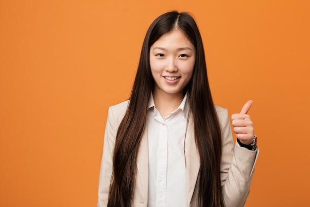 Mujer china joven del negocio que sonríe y que levanta el pulgar para arriba