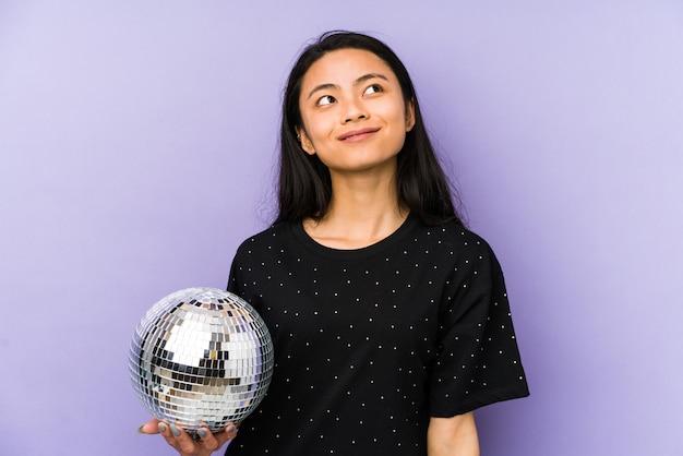 Mujer china joven en una pared púrpura sorprendida y conmocionada.