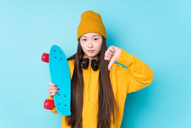 La mujer china joven del patinador aisló mostrar un gesto de la aversión, pulgares abajo. concepto de desacuerdo