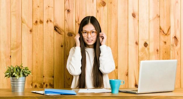 Mujer china joven que estudia en su escritorio que cubre los oídos con las manos.