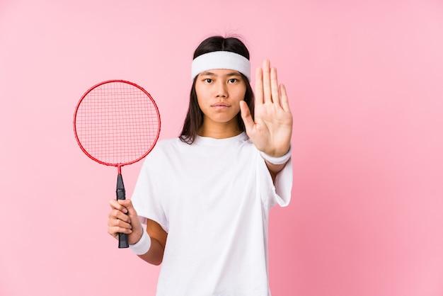 Mujer china joven que juega a bádminton en una pared rosada que se coloca con la mano extendida que muestra la señal de stop, previniéndole.