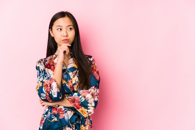 La mujer china joven que llevaba un pijama del kimono aisló mirar de lado con expresión dudosa y escéptica.