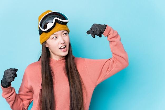 La mujer china joven que llevaba la ropa del esquí aisló levantar el puño después de una victoria, concepto del ganador.