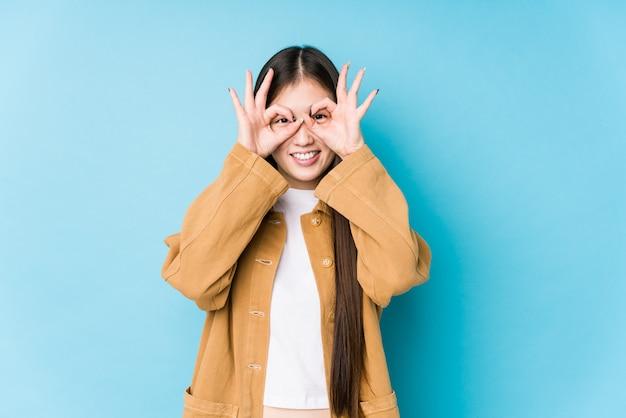 Mujer china joven que presenta en una pared azul aislada que muestra la muestra aceptable sobre ojos
