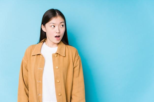 La mujer china joven que presenta en una pared azul aisló ser sorprendida debido a algo que ella ha visto.