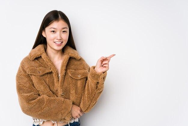 La mujer china joven que presentaba en una pared blanca aisló la sonrisa que señalaba alegremente con el índice lejos.