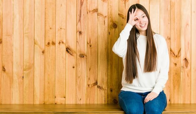 La mujer china joven que se sentaba un lugar de madera excitó guardar ojo aceptable del gesto.
