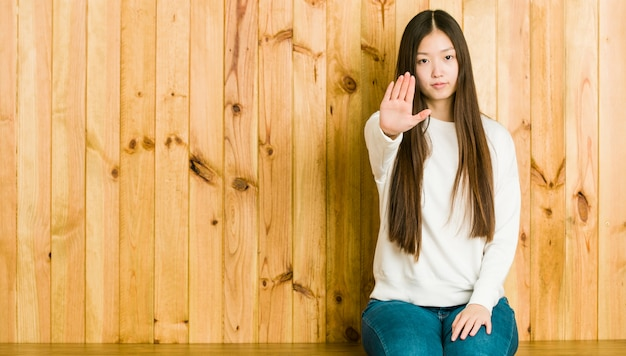 Mujer china joven que se sienta en un lugar de madera que se coloca con la mano extendida que muestra la señal de stop, previniéndole.