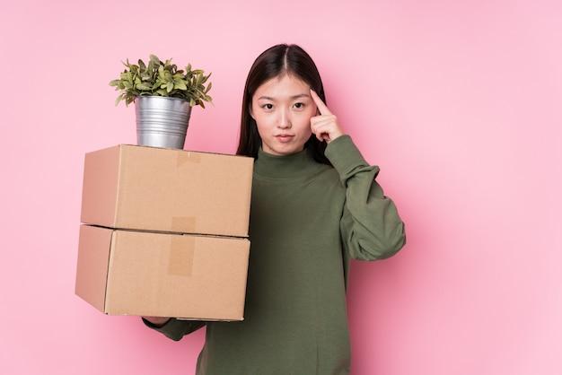 La mujer china joven que sostenía las cajas aisló señalar el templo con el dedo, pensando, centrado en una tarea.