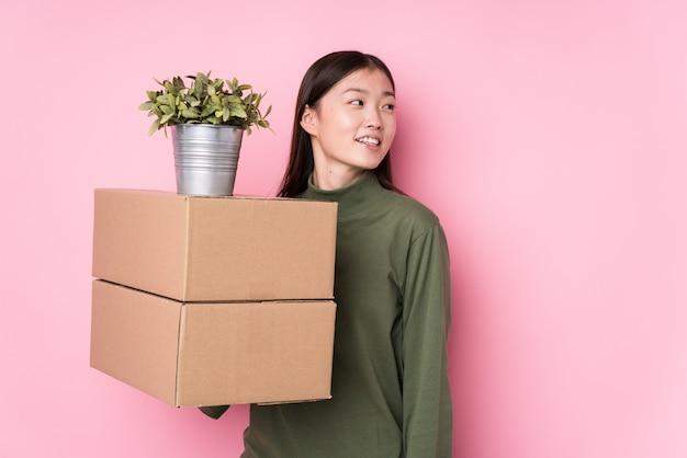La mujer china joven que sostiene las cajas aisladas mira a un lado sonriente, alegre y agradable.