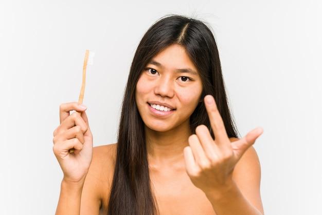 La mujer china joven que sostiene un cepillo de dientes aislado señalando con el dedo a usted como si invitara se acerque.