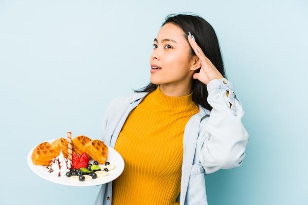 Mujer china joven que sostiene la galleta aislada en el espacio azul que se sorprende, ella ha recordado la reunión importante.