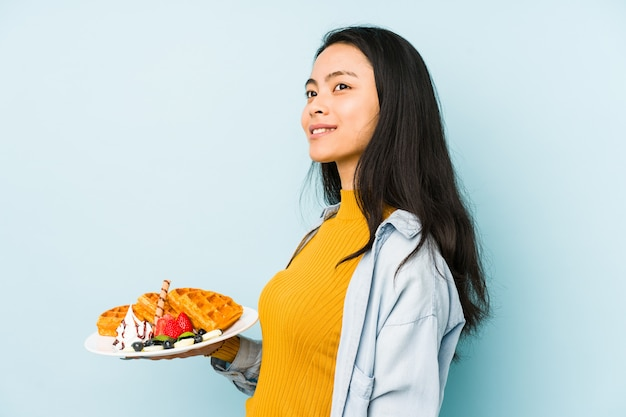 Mujer china joven que sostiene la galleta en la pared azul que mira de lado con expresión dudosa y escéptica.