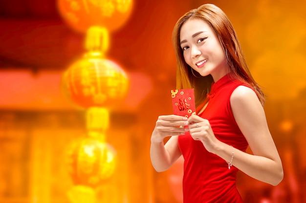 Mujer china joven en vestido cheongsam sosteniendo angpao