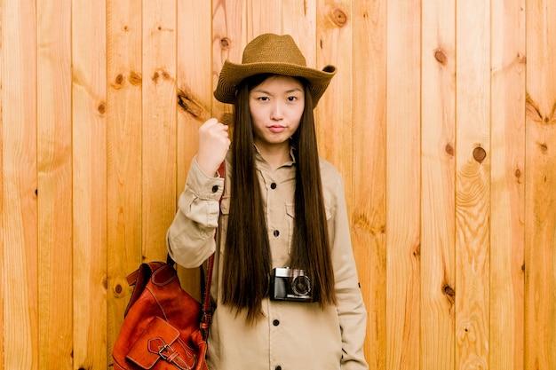 Mujer china joven del viajero que muestra el puño con la expresión facial agresiva.