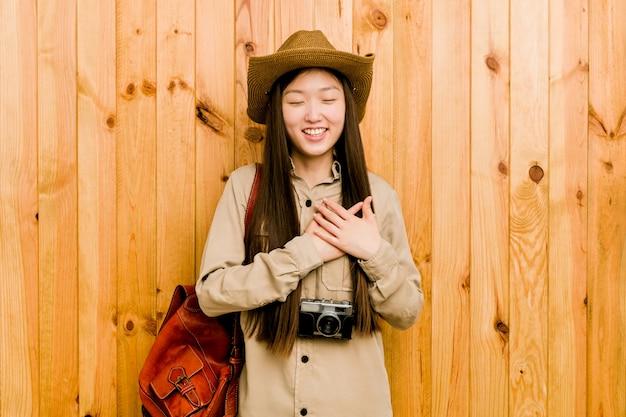 Mujer china joven del viajero que ríe manteniendo las manos en el corazón, concepto de felicidad.