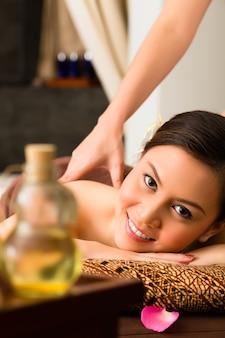 Mujer china en masaje de bienestar con aceites esenciales.