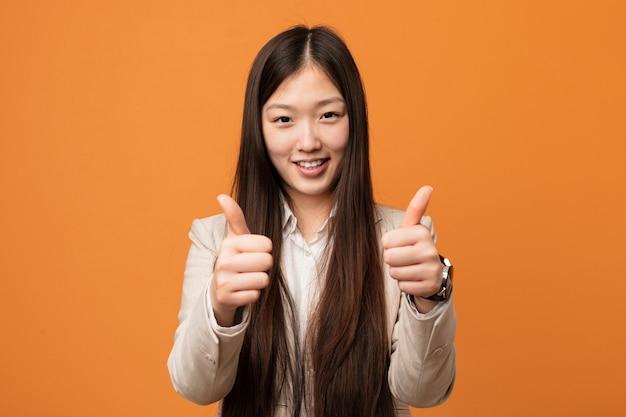 La mujer china del negocio joven con los pulgares sube, anima sobre algo, apoya y respeta el concepto.