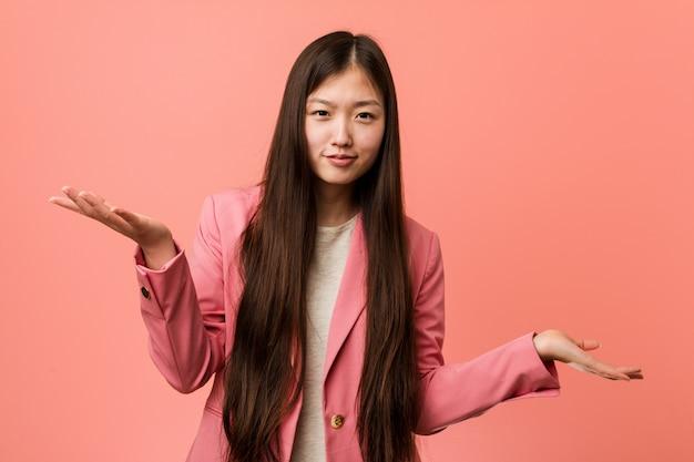 Mujer china del negocio joven que lleva el traje rosado que duda entre dos opciones.