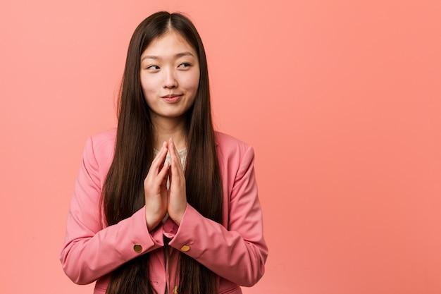 Mujer china del negocio joven que lleva el traje rosado que hace el plan en mente, creando una idea.