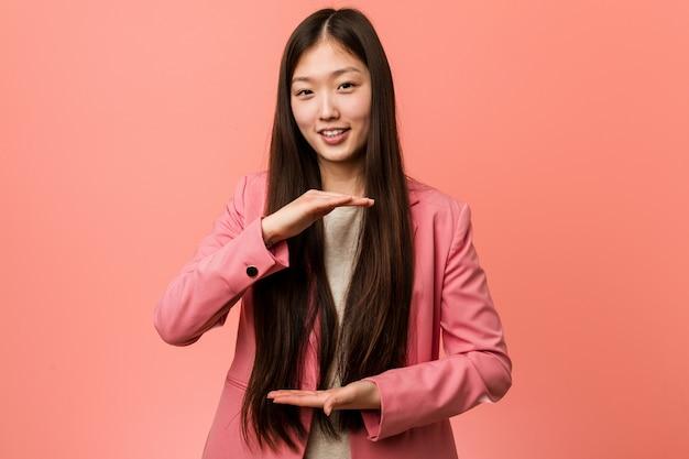 Mujer china del negocio joven que lleva el traje rosado que lleva a cabo algo con ambas manos, presentación del producto.