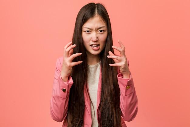 Mujer china de negocios joven vistiendo traje rosa molesto gritando con manos tensas.