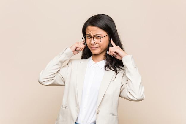 Mujer china de negocios jóvenes cubriendo las orejas con las manos.