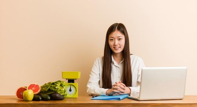 Mujer china del nutricionista joven que trabaja con su computadora portátil feliz, sonriendo y alegre.
