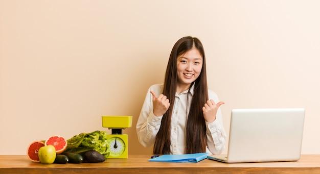 Mujer china del nutricionista joven que trabaja con su computadora portátil que levanta ambos pulgares para arriba, sonriendo y confidente.