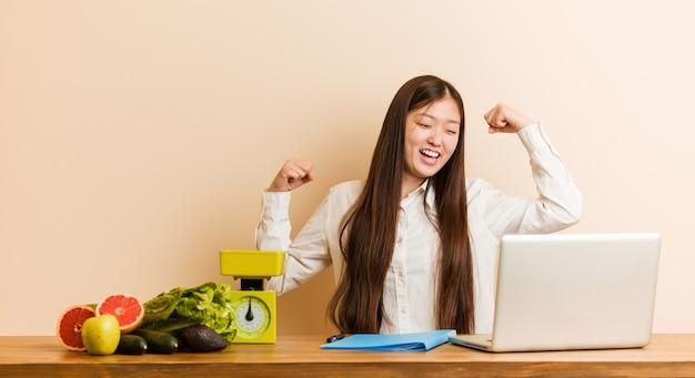Mujer china del nutricionista joven que trabaja con su computadora portátil que levanta el puño después de una victoria, concepto del ganador.