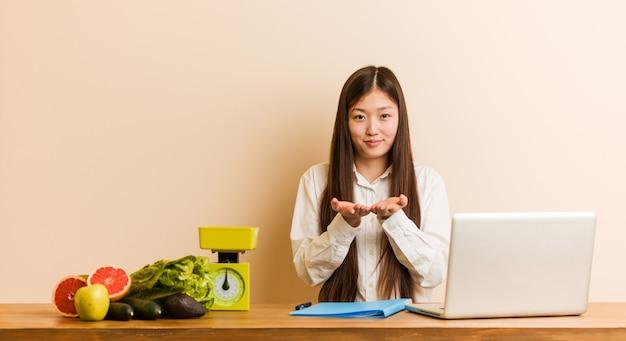 Mujer china del nutricionista joven que trabaja con su computadora portátil que lleva a cabo algo con las palmas