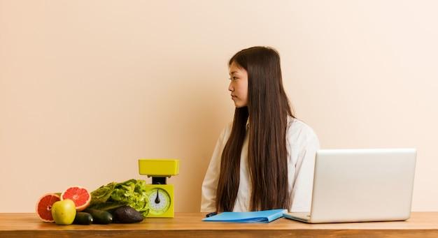 La mujer china del nutricionista joven que trabaja con su computadora portátil que mira a la izquierda, de lado presenta.
