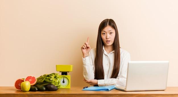 Mujer china nutricionista joven que trabaja con su computadora portátil que tiene una gran idea