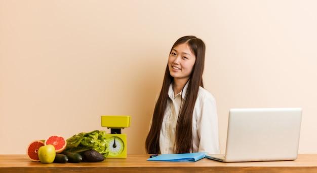 La mujer china nutricionista joven que trabaja con su computadora portátil se ve a un lado sonriente, alegre y agradable.