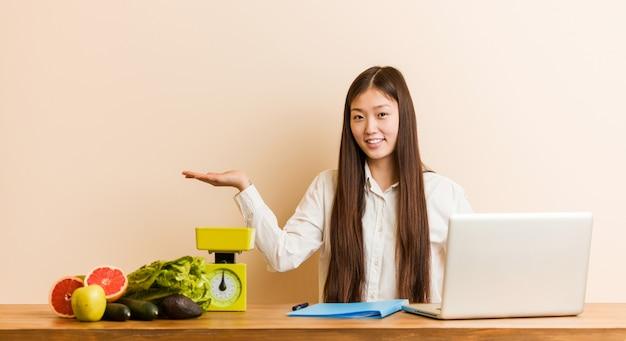 Mujer china nutricionista joven que trabaja con su computadora portátil