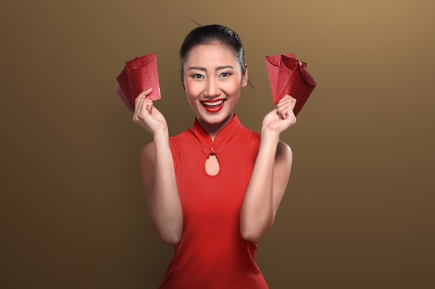 Mujer china en ropa tradicional sosteniendo angpao.