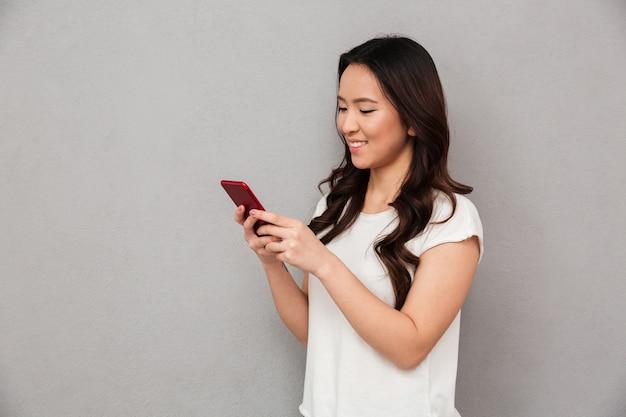 Mujer china sonriente contenta en camiseta casual escribiendo mensajes de texto o desplazando la red social con un teléfono inteligente, aislado sobre una pared gris