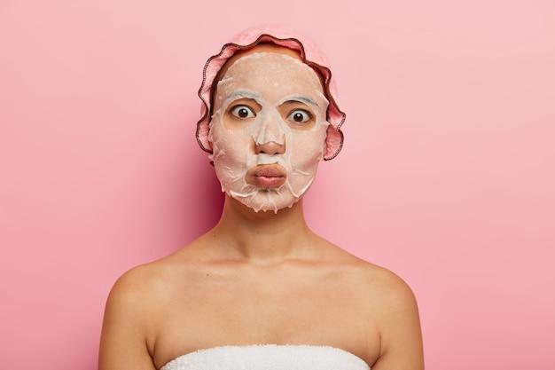 La mujer china sorprendida mantiene los labios doblados, hace muecas, usa una mascarilla facial de papel para refrescarse, tiene una tez saludable, una piel suave y perfecta, usa una tapa de ducha, envuelta en una toalla después del baño