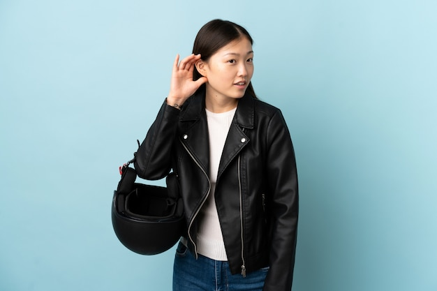 Mujer china sosteniendo un casco de motocicleta sobre pared azul aislada escuchando algo