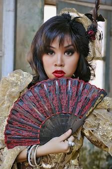 Mujer china vestida con un traje victoriano que sostiene un abanico, dispara al edificio grunge